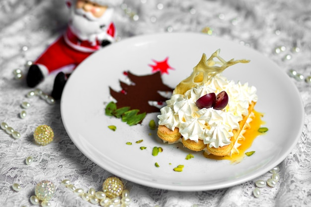 Prato de biscoitos com creme ao lado da árvore de natal em pó de café Foto gratuita