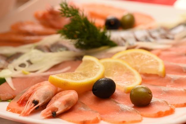 Prato de camarão, salmão com azeitonas e limão, aperitivo Foto Premium
