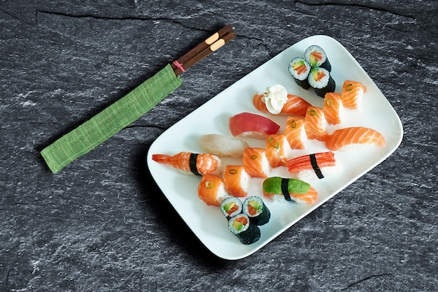 Prato de deliciosos sushis e maki sobre textura de fundo Foto Premium