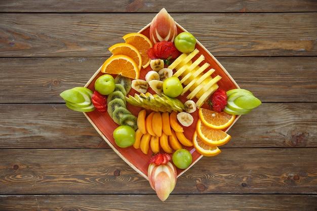 Prato de fatias de frutas com maçã, laranja, morango Foto gratuita