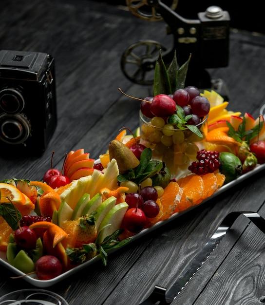 Prato de frutas em uma mesa de madeira Foto gratuita