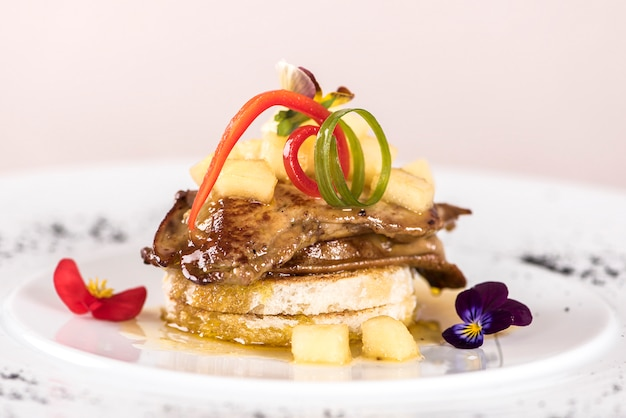 Prato de luxo com fígado de pato, abacaxi e pedaços de manga, molho doce, colocado no torrado Foto Premium