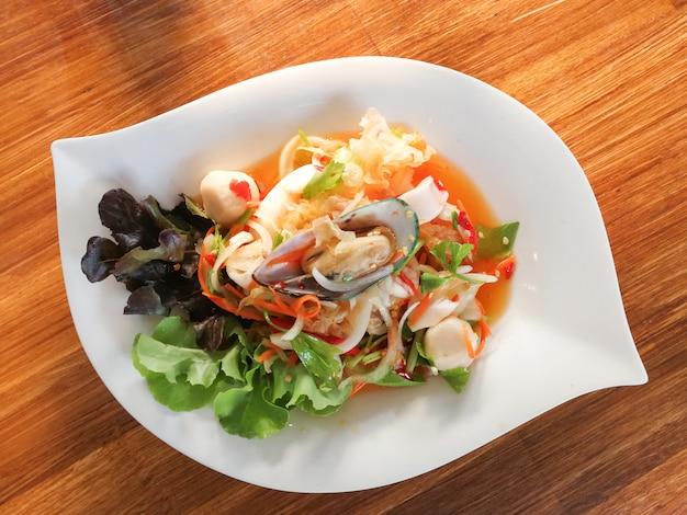Prato de marisco de mistura de salada picante com camarão de mexilhão de lula e vegetais frescos servidos na mesa de jantar Foto Premium
