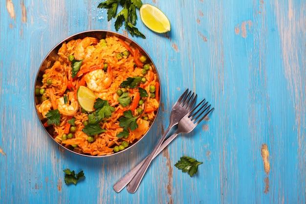 Prato de paella espanhola tradicional com frutos do mar, ervilhas, arroz e frango Foto Premium