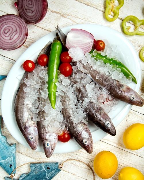 Prato de peixe cru coberto com pimenta, tomate cereja e cebola vermelha Foto gratuita