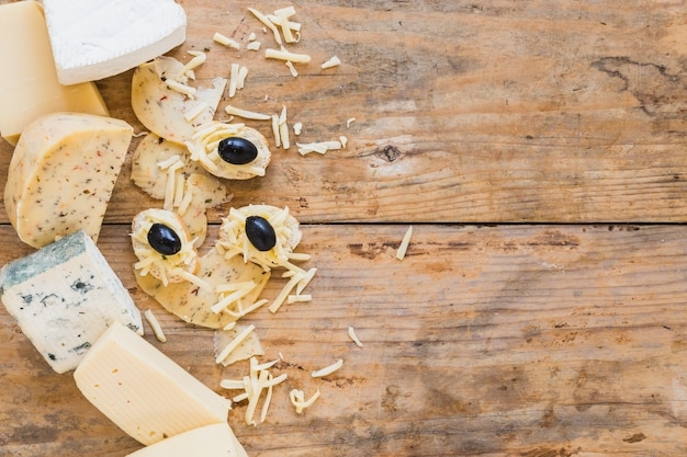 Prato de queijo com mini sanduíches na mesa de madeira Foto gratuita