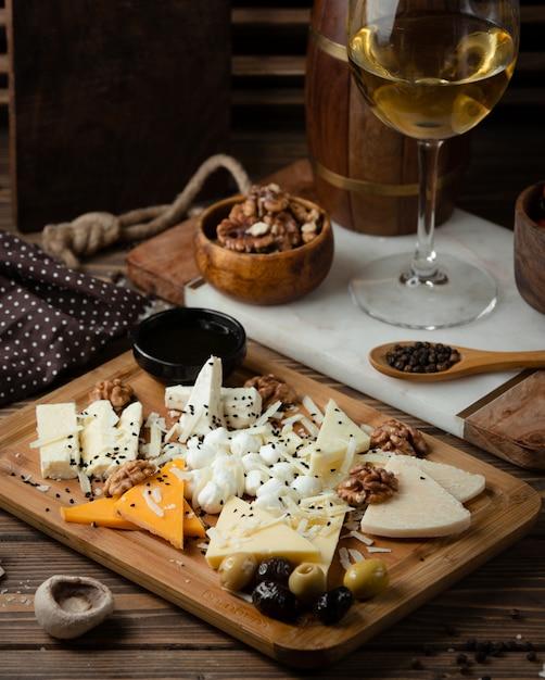 Prato de queijo na tábua de madeira com vinho branco Foto gratuita