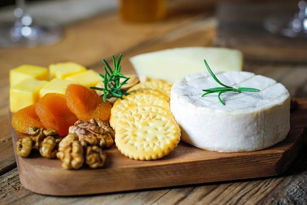 Prato de queijo, queijo camembert, alecrim, bolachas, damasco seco e nozes Foto gratuita