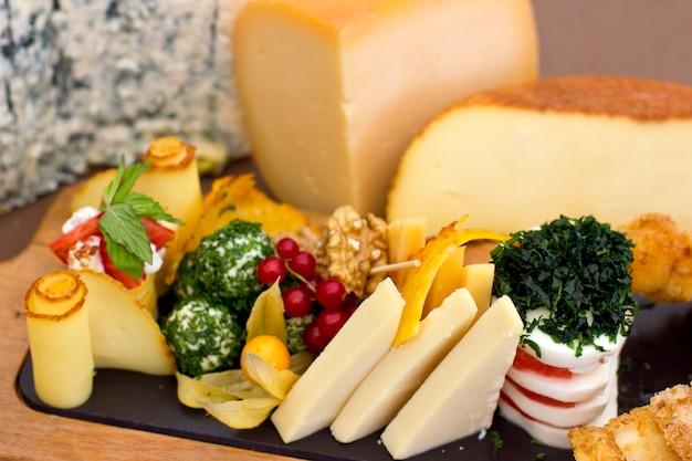 Prato de queijo: roquefort com mofo azul, queijo cheddar, queijo defumado, mussarela em uma placa de madeira. Foto Premium
