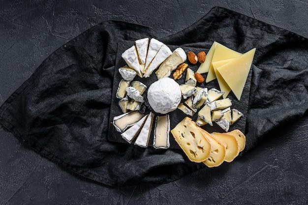 Prato de queijo servido com nozes e figos. aperitivo francês. fundo preto. vista do topo Foto Premium