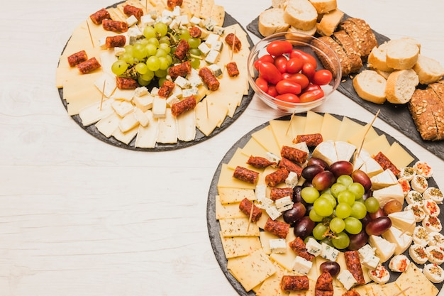 Prato de queijo servido com tomate, fatias de pão e enchidos na mesa de madeira Foto gratuita
