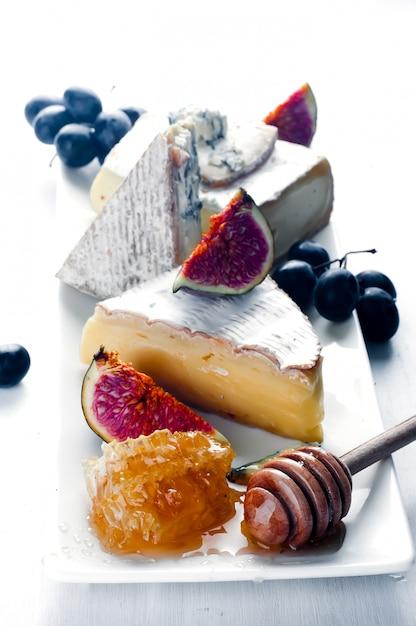 Prato de queijo variedade de vários tipos e mel Foto Premium