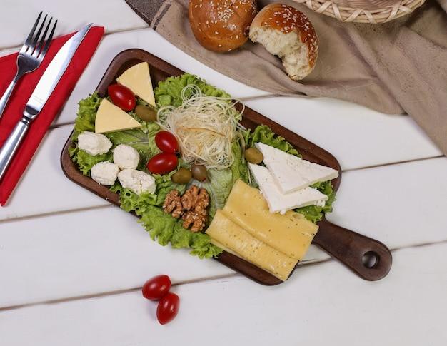 Prato de queijos com tomates, nozes e azeitonas, com talheres e pão em volta. Foto gratuita