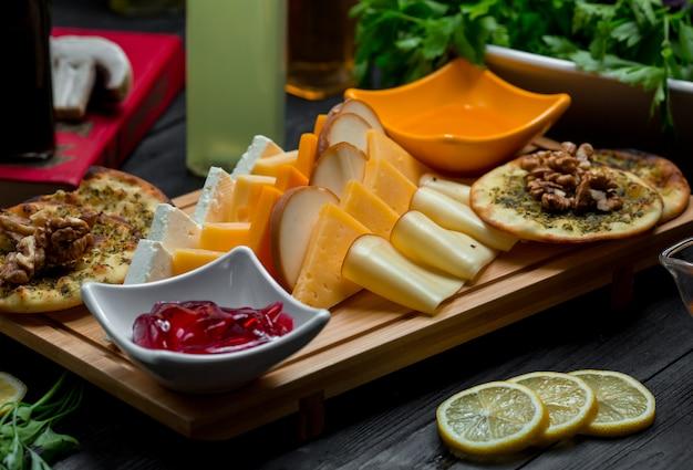 Prato de queijos com variações de queijos, bolachas, nozes e geléia de morango Foto gratuita
