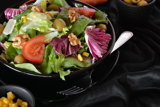 Prato de salada com alface, tomate, azeitonas e azeite. em um pano preto Foto Premium