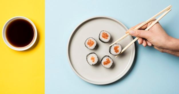 Prato de sushi japonês com pauzinhos e molho de soja Foto gratuita