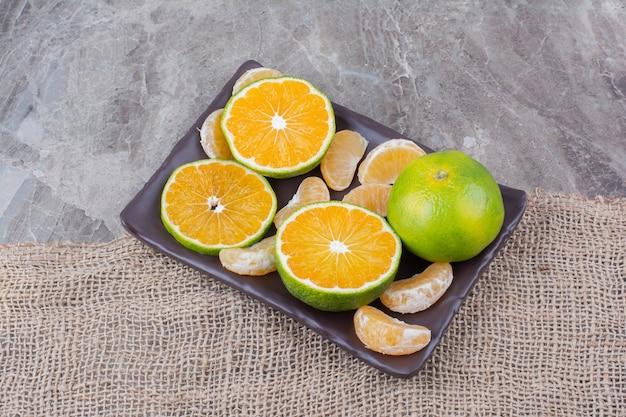 Prato de tangerinas frescas em fundo de pedra. Foto gratuita