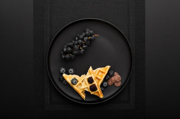 Prato escuro com waffles e uvas em um pano escuro Foto gratuita