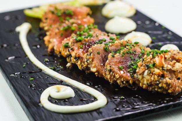 Prato japonês de atum tataki servido em um prato de pedra preta Foto Premium