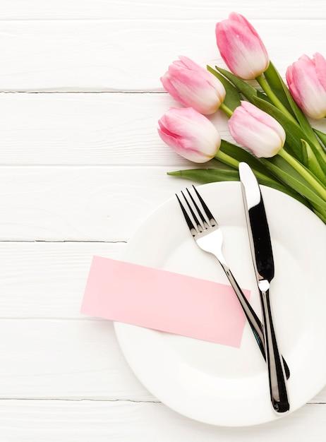 Prato liso leigo com talheres e tulipas ao lado Foto gratuita
