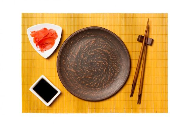 Prato marrom redondo vazio com palitos para sushi, gengibre e molho de soja na esteira de bambu amarelo Foto Premium