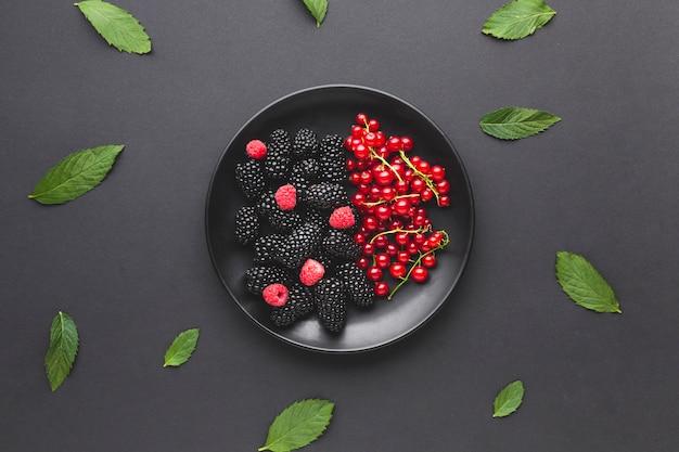 Prato plano de frutas frescas com folhas Foto gratuita