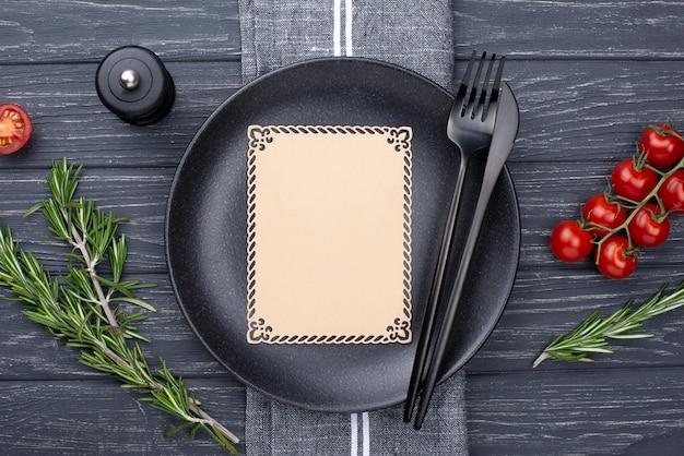 Prato plano leigo com talheres e tomate Foto gratuita