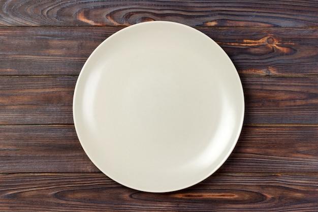 Prato redondo fosco vazio na mesa de madeira. vista do topo Foto Premium
