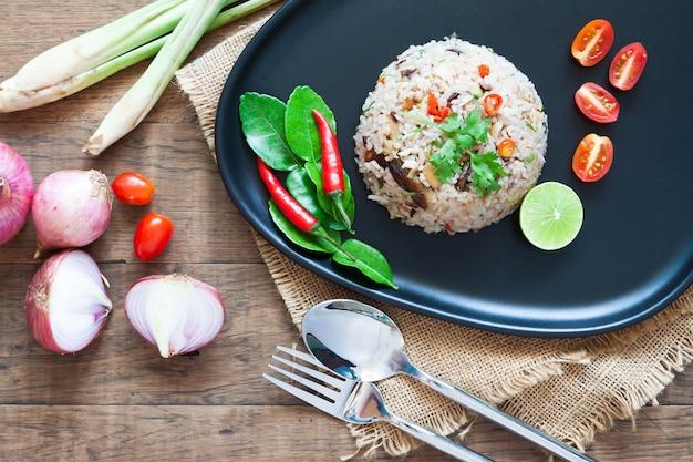 Prato tailandês especial. arroz frito com cavala, pimenta, folhas de limão, cebola e ervas tailandesas. vista do topo Foto Premium