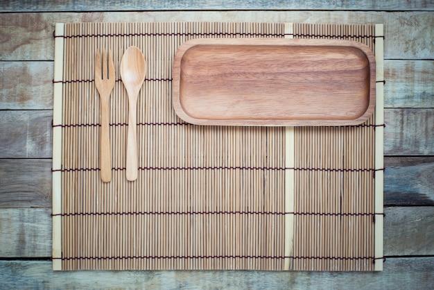 Prato vazio com garfo e colher na mesa de madeira Foto Premium