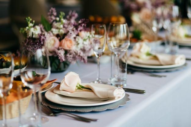 Prato vazio, copos, garfos, guardanapo e flores na mesa coberta com toalhas de mesa brancas Foto Premium