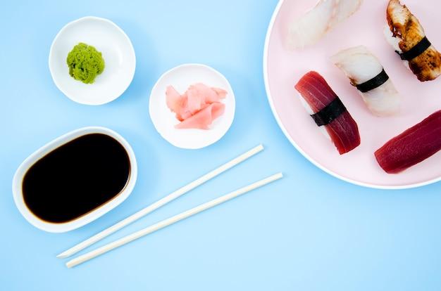 Pratos com sushi e molho de soja em um fundo azul Foto gratuita