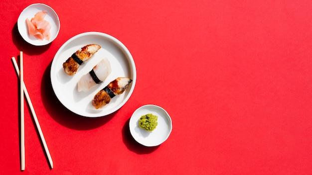 Pratos com sushi e wasabi em um fundo vermelho Foto gratuita