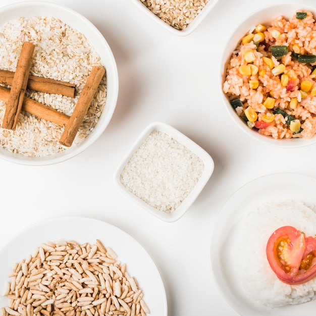 Pratos de arroz com tigelas de arroz crus no fundo branco Foto gratuita