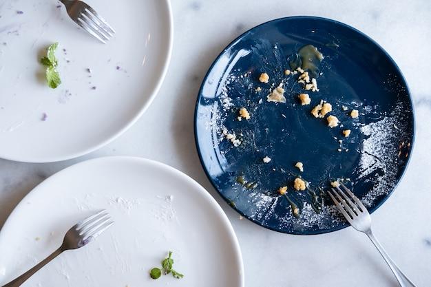 Pratos de bolo vazio com garfo na mesa Foto Premium