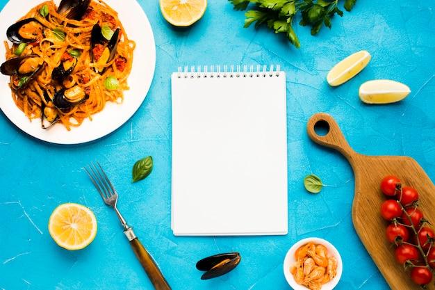 Pratos de frutos do mar planos com notebook Foto gratuita