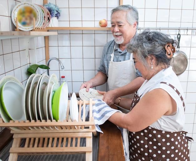 Pratos de lavagem dos pares superiores felizes asiáticos mais velhos no dissipador em casa na cozinha em casa. Foto Premium
