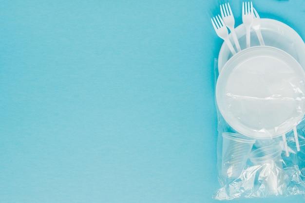 Pratos de plástico sobre um fundo azul. louça descartável Foto Premium