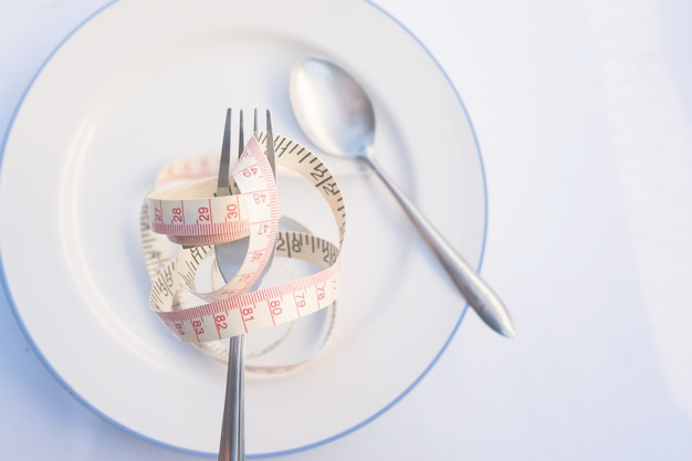 Pratos de receita dietética para comer. garfo é embrulhado em fita métrica amarela no prato com colher Foto Premium