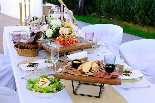 Pratos deliciosos em bandejas de madeira e bebidas em uma mesa de banquete em um restaurante. Foto Premium