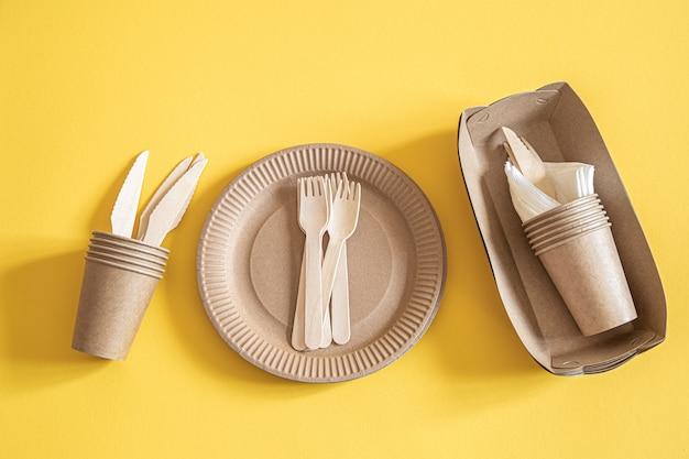 Pratos descartáveis ecológicos feitos de papel em um fundo laranja. Foto gratuita