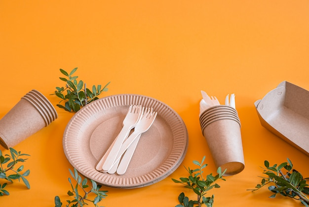 Pratos descartáveis ecológicos feitos de papel em uma parede laranja Foto gratuita
