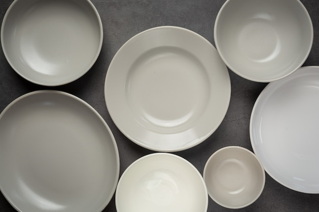 Pratos e tigelas vazios redondos e brancos na superfície escura Foto gratuita