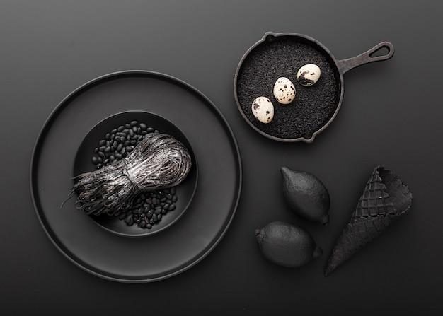 Pratos escuros com macarrão e ovos com feijão em um fundo escuro Foto gratuita