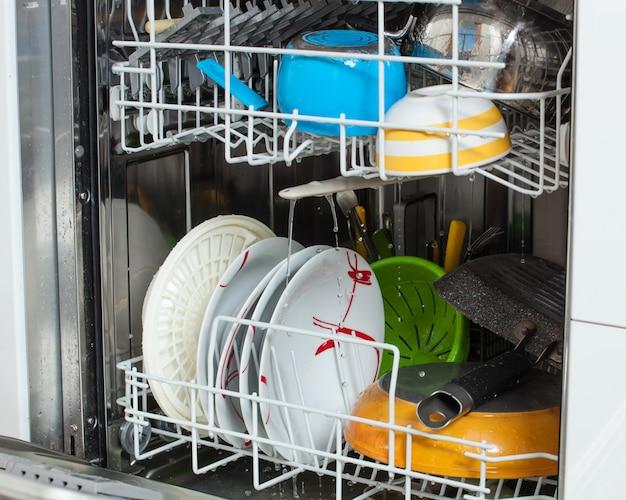 Pratos sujos carregados em uma máquina de lavar louça Foto Premium