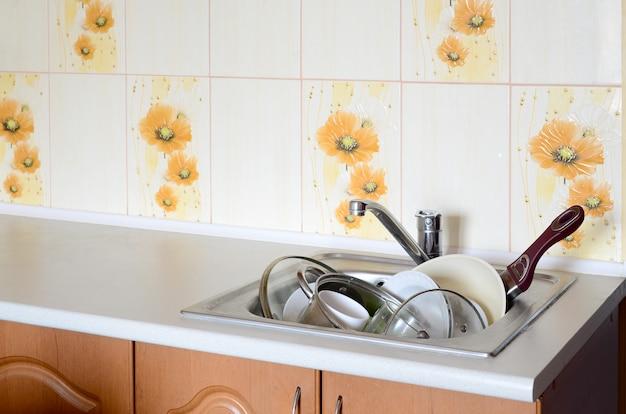 Pratos sujos e utensílios de cozinha sujos enchiam a pia da cozinha Foto Premium