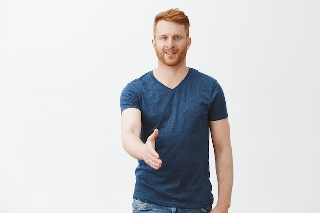 Prazer em conhecê-lo. homem europeu bonito, charmoso e simpático, ruivo, com cerdas, puxando a mão em pose de aperto de mão Foto gratuita
