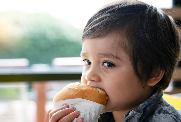 Pré-escolar garoto comendo hambúrguer sentado no café Foto Premium