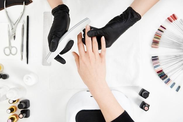 Prego tecnologia arquivando unhas com lixa de unha. ferramentas de manicure profissional. Foto gratuita