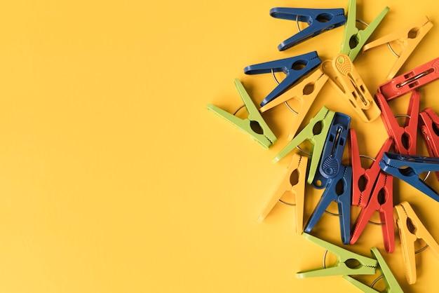 Prendedor de roupa vista superior com fundo amarelo Foto gratuita
